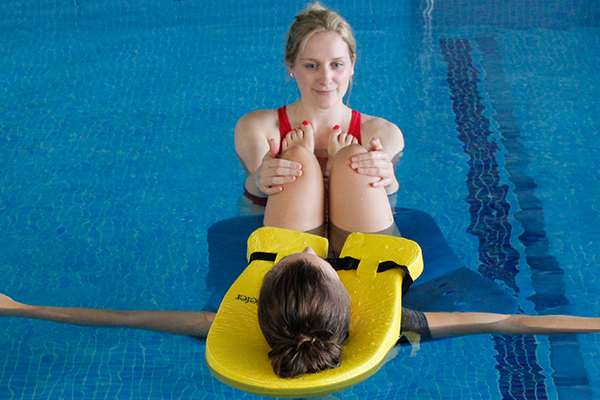 Female Recieves Hydrotherapy to aid recovery in pool.